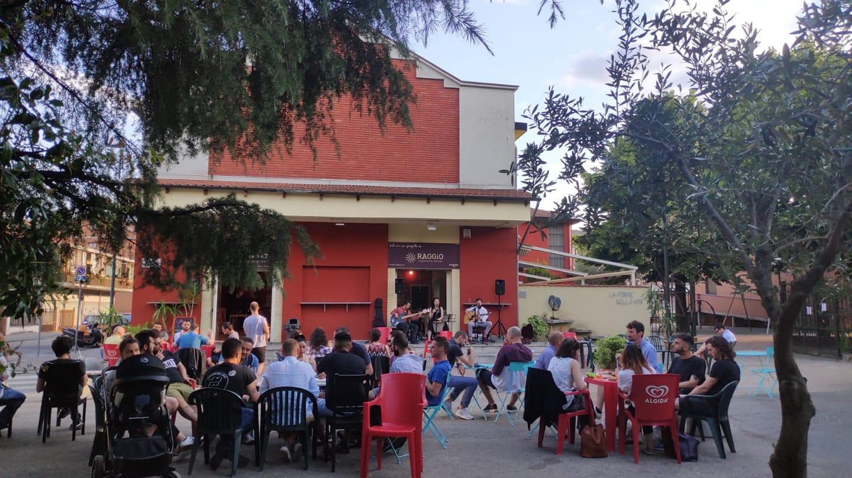 Al Baretto Torino, esterno del locale di giorno - tavolini all'aperto con gente seduta, cameriere che passa tra i tavoli e musicisti che suonano sullo sfondo