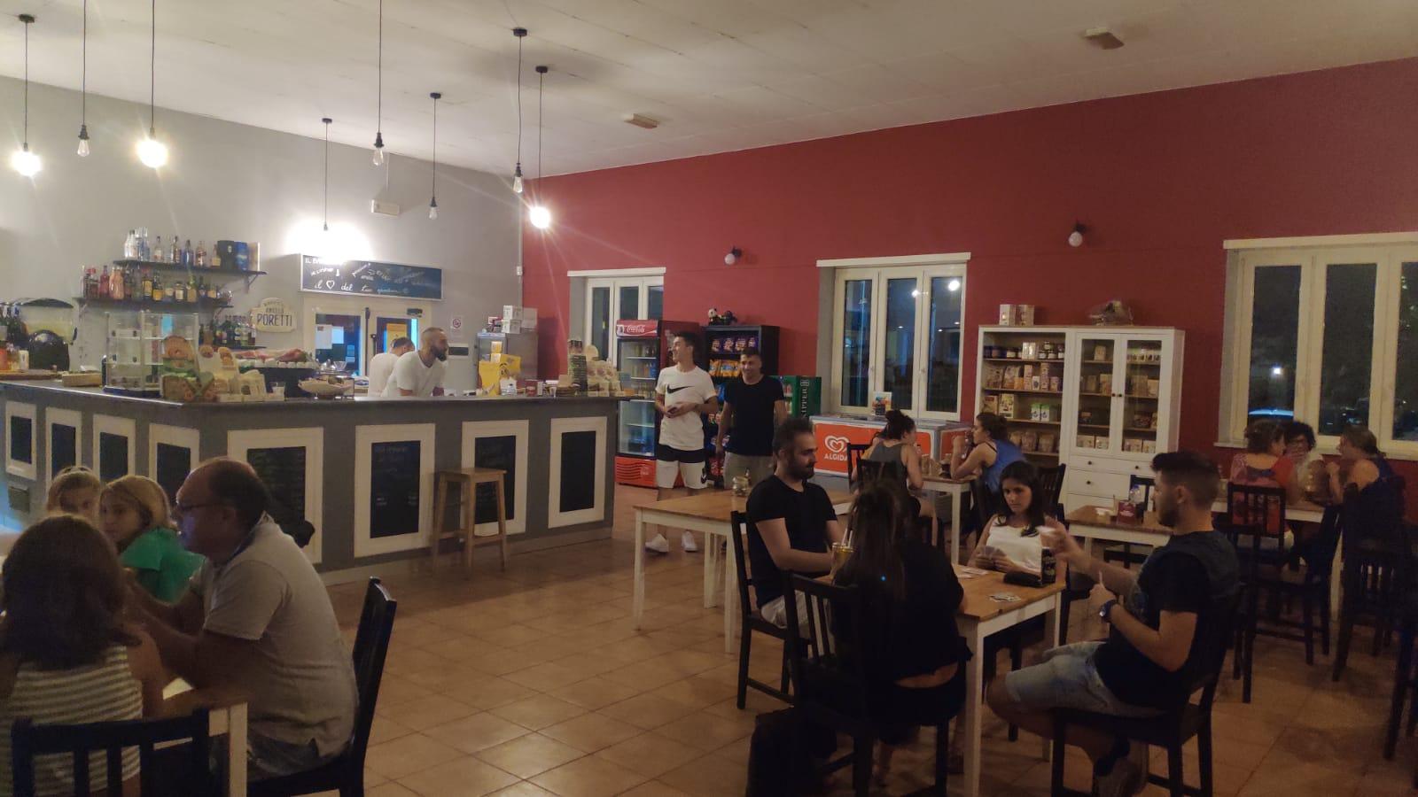 Al Baretto Torino, interno del locale di sera: bancone del bar con baristi che parlano con i clienti e tavoli con gente seduta - Cooperativa Sociale Raggio