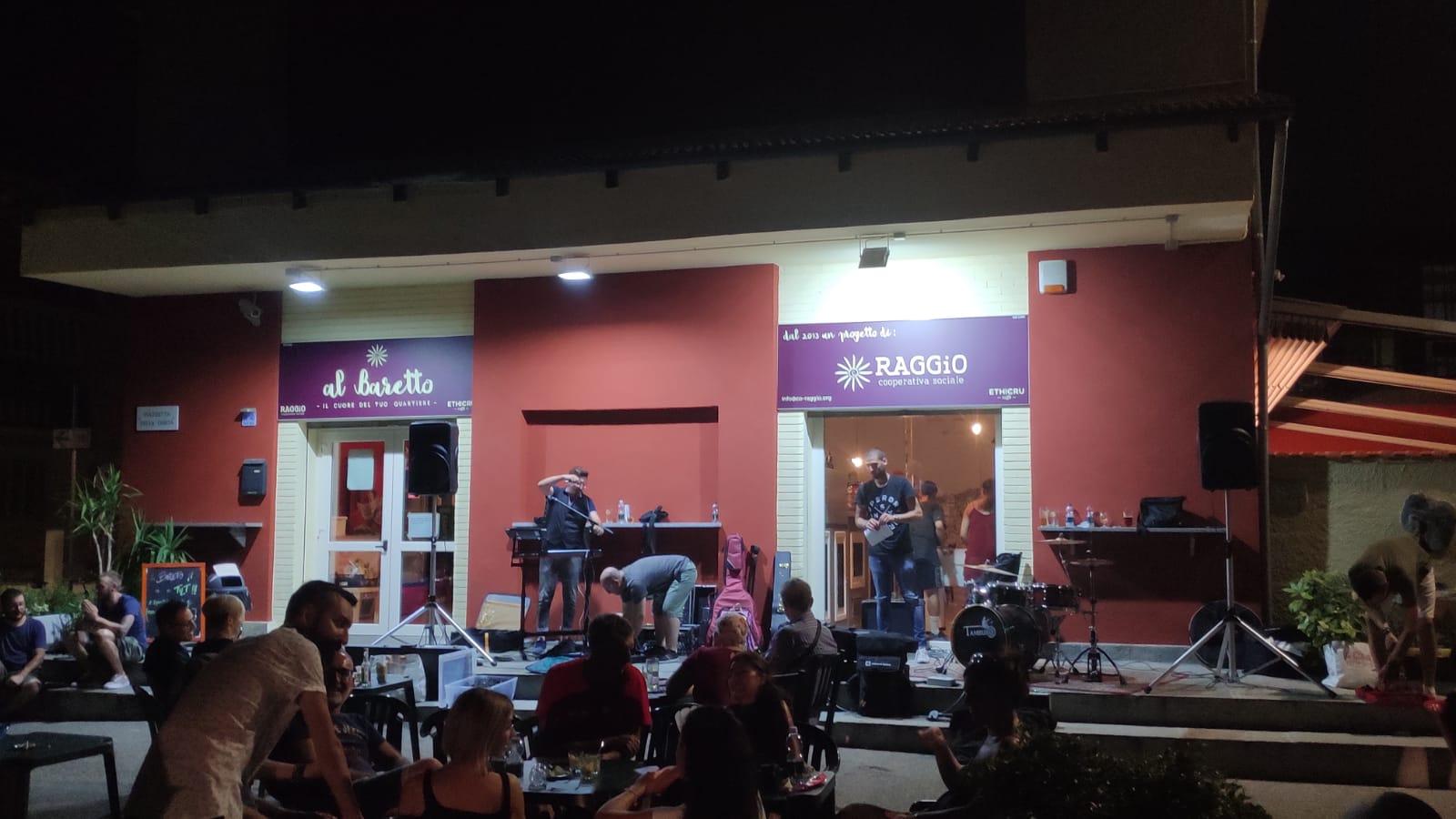 Al Baretto Torino, esterno del locale di sera - tavolini all'aperto con gente seduta e musicisti che suonano