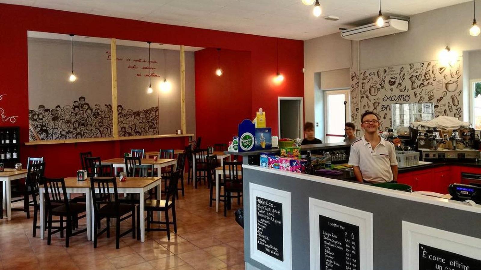 Al Baretto Torino, interno del locale: prospettiva della sala con i tavoli e il bancone del bar con il barista sorridente