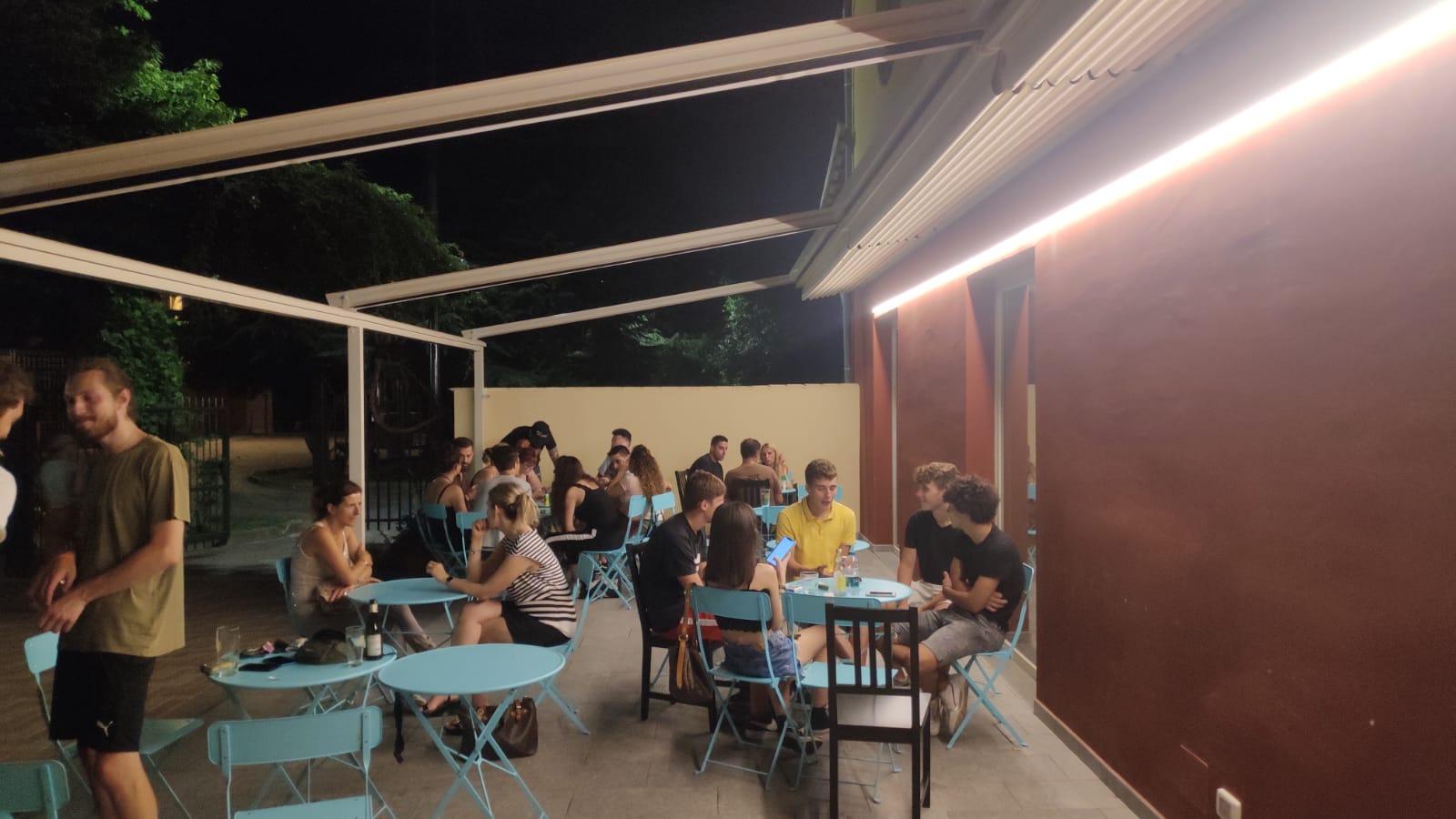 Al Baretto Torino, esterno del locale di sera - tavolini all'aperto nel dehor con gente seduta