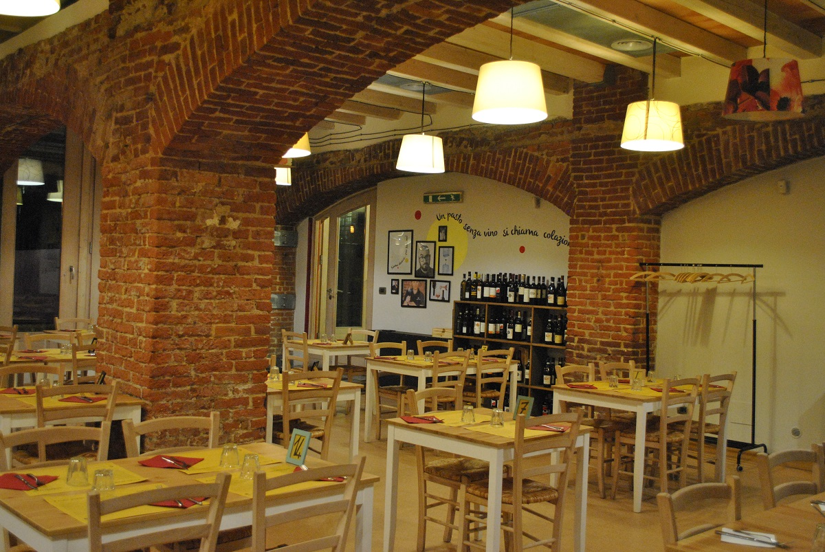 Interno dell'Osteria e Caffetteria Andirivieni, un progetto della Cooperativa Sociale Raggio di Torino: vista della sala con tavoli apparecchiati e cantinetta portabottiglie sullo sfondo