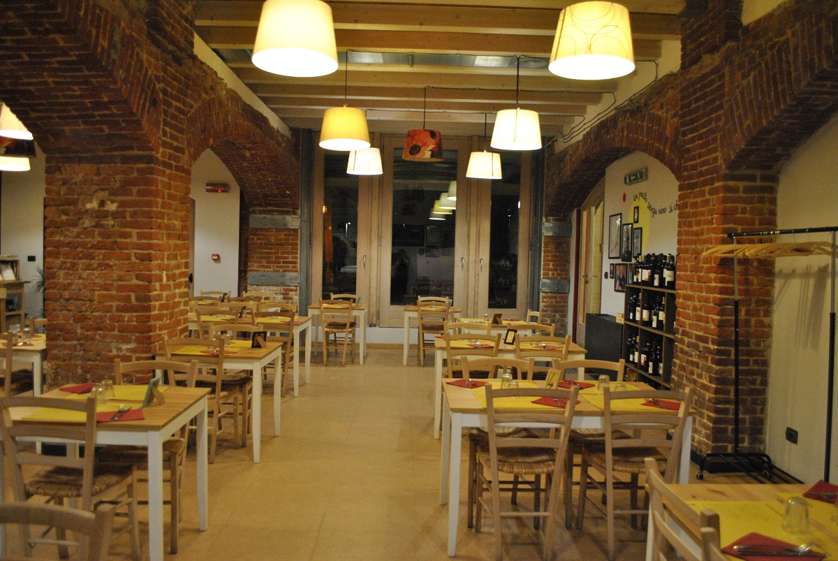 Interno dell'Osteria e Caffetteria Andirivieni a Torino: vista della sala con tavoli apparecchiati