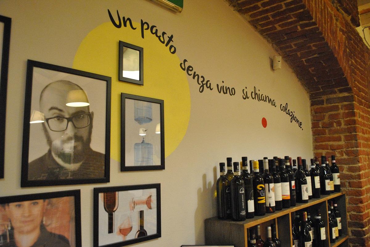 Dettaglio dell'Osteria e Caffetteria Andirivieni a Torino: fotografie appese e grafica sul muro sopra la cantinetta porta bottiglie