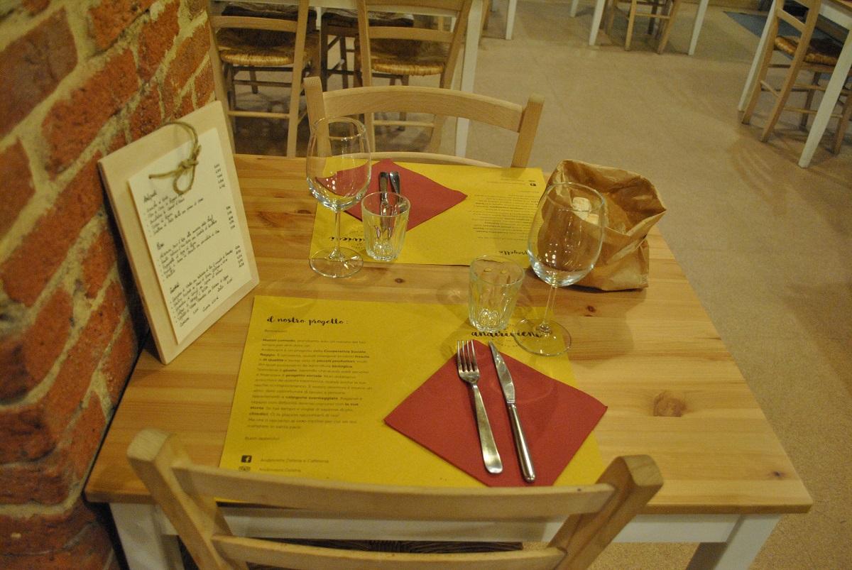 Dettaglio dell'Osteria e Caffetteria Andirivieni a Torino: tavola apparecchiata con posate su tovaglilo rosso, bicchieri, tovaglietta, menù sulla lavagnetta e pane nel sacchetto