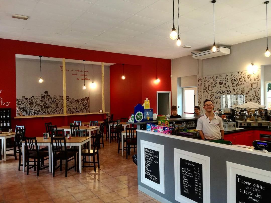 Al Baretto, un progetto di Cooperativa Sociale Raggio di Torino, interno del locale: prospettiva della sala con i tavoli e il bancone del bar con il barista sorridente