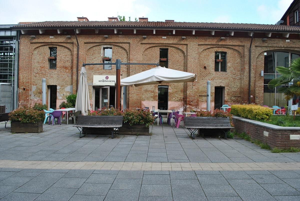 Dehor esterno dell'Osteria e Caffetteria Andirivieni, un progetto di Cooperativa Sociale Raggio di Torino: tavolini esterni sotto gli ombrelloni, aiuole fiorite e panchine e l'entrata del locale sullo sfondo