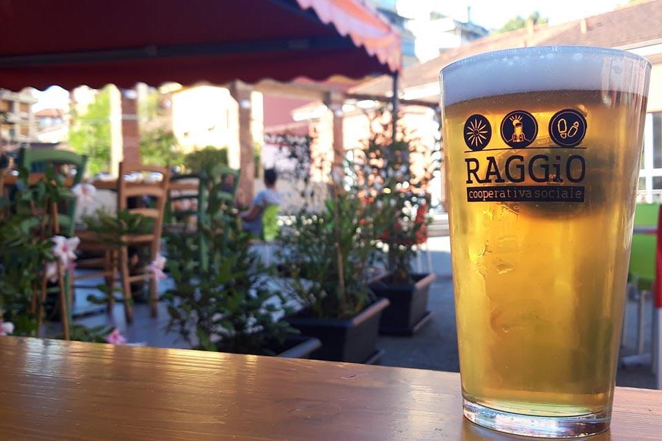 Bicchiere di birra su un tavolino di Al Cecchi, la piola oltre frontiera